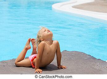 little girl sunbathing on a rock near pool