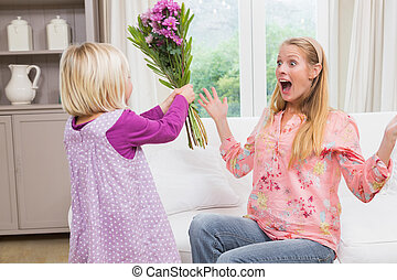 Little girl surprising her mother with flowers at home in ...