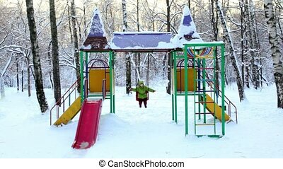 Little girl sway on chain swing at childrens playground,...