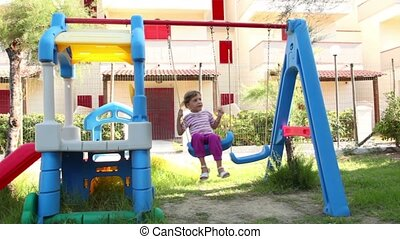 Little girl swaying at swing on playground at summer