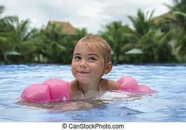 Little girl swim in a pool