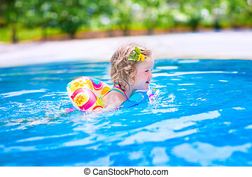 Little girl swimming in a pool - Adorable little girl with...
