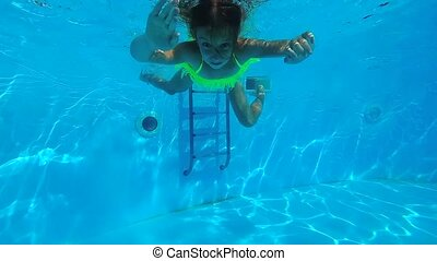 Little girl swimming under the water in swimming pool....