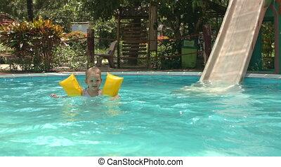Little Girl Swims in Pool near Water-slide against Plants -...