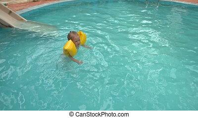Little Girl Swims in Pool near Water-slide at Hotel - little...