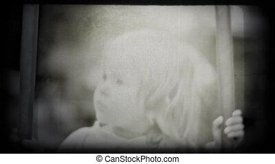 Little girl swinging and smiling, vintage styled shot.
