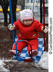 little girl swinging at the playground