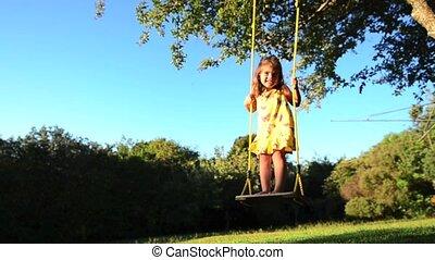 Little girl swinging.