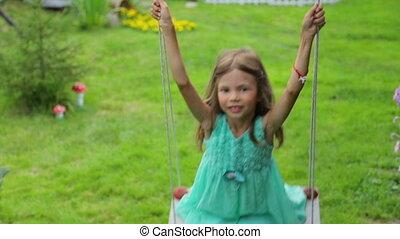 Little girl swinging in garden