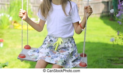 Little girl swinging in garden
