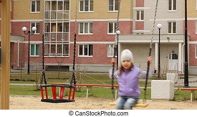 Little girl swinging in slow motion