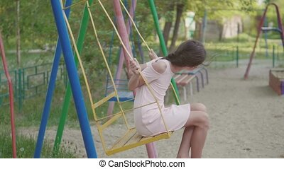 little girl swinging on an old swing slow-motion video. schoolgirl playing on the street swinging on the swing childhood outdoors lifestyle. girl and swing concept