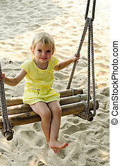 Little girl swinging with the beach in the background