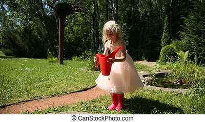 Little girl takes a red watering can