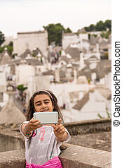 Little girl takes a selfie in front of the trulli of Alberobello