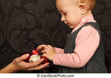 Little girl takes Christmas toys from the hands of mothers. Close up. Horizontal format.