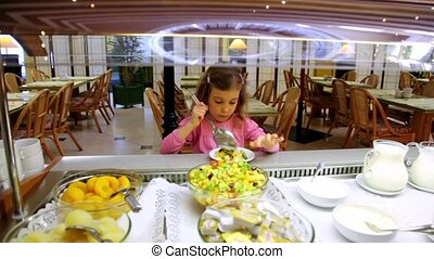 Little girl takes food and put it on plate at breakfast time
