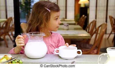 Little girl takes jug with milk and pours it in plate at restaurant