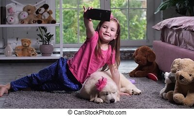 Little girl taking selfie photo with puppy at home - Cute...