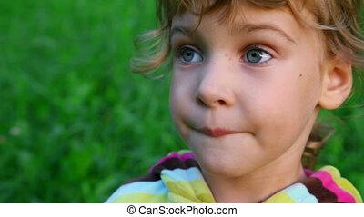 little girl talking on green grass background