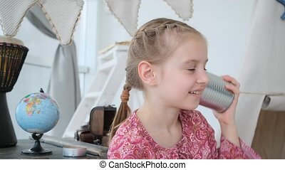 Little girl talking on handmade phone made from can and thread in light room