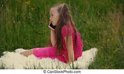 little girl talking on the phone - little girl in a pink...