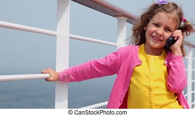 Little girl talks by cell phone and holds fence on deck...
