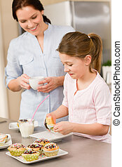 Little girl taste sprinkles cupcakes with mum