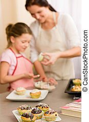 Little girl taste sprinkles decorating cupcakes with mother...