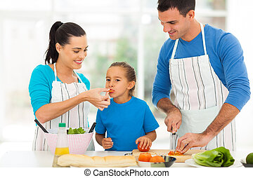 little girl tasting tomato while parents cooking - little...