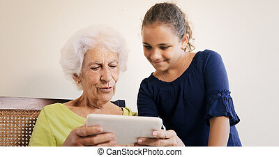 Little Girl Teaching Grandmother How To Use Tablet For Internet