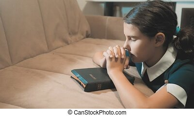 Little girl teenager praying in the night. Little girl hand praying. little girl holy bible prays with bible in her hands. catholicism sacred holy bible. children and religion upbringing faith symbol. Little girl with praying. Peace, hope lifestyle , dreams concept
