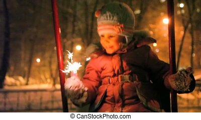 little girl teetering and holding sparkler in hand, night ...