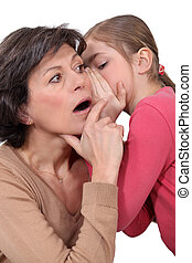 little girl telling a secret to her mother