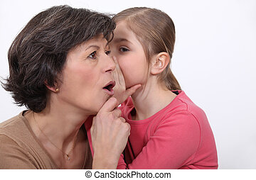 little girl telling her mother a secret