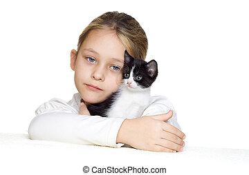 little girl tenderly embraces a kitten