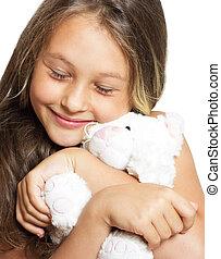 little girl tenderly embraces plush toy