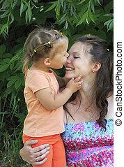Little girl tenderly kisses and hugs his mother.