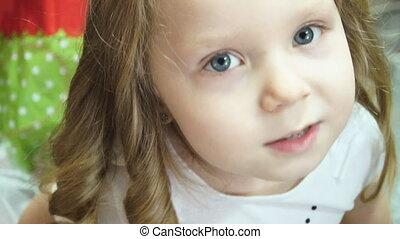 Little girl. The mother raises the girl's hair