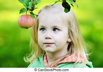 little girl thoughtfully looks at the apple in garden