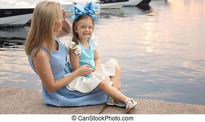 little girl three years sitting on the lap of the mother with long blond hair
