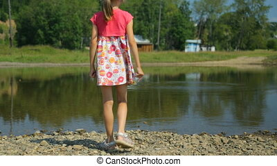 Little girl throwing stones into water