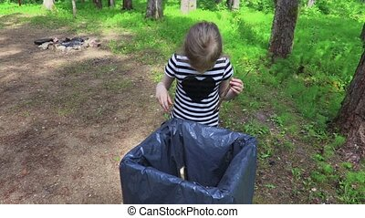 Little girl throws garbage in the park in the container