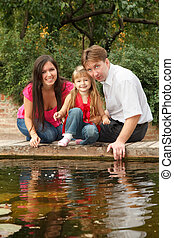 Little girl together with parents sits on the bank of reservoir in summer garden.