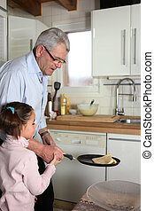 Little girl tossing pancakes with her granddad