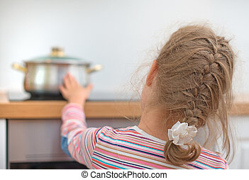 Little girl touches hot pan on the stove. Dangerous...