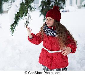 Little girl touching snow on fir-tree branch