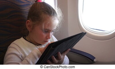 Little girl traveling in airplane with a tablet