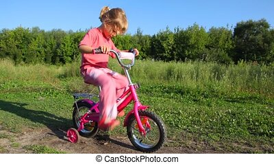 girl treadling stopped bicycle, boy rides to her