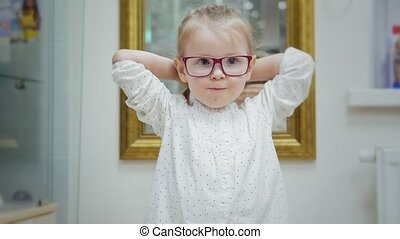 Little girl tries glasses near mirror - shopping in...